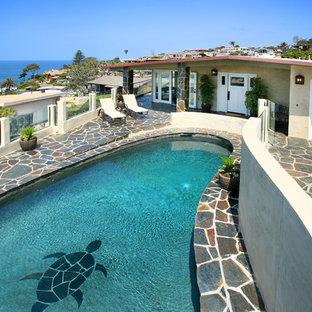 Diseño de piscina bohemia, a medida, en patio delantero, con adoquines de piedra natural
