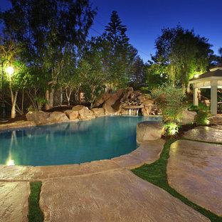 Стильный дизайн: естественный бассейн произвольной формы в стиле рустика с водной горкой - последний тренд