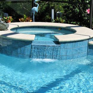 Ejemplo de piscina con fuente natural, moderna, grande, redondeada, en patio trasero