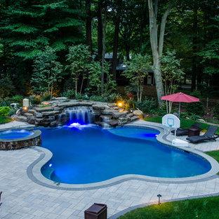 Foto de piscina con fuente natural, clásica renovada, grande, a medida, en patio trasero, con adoquines de piedra natural