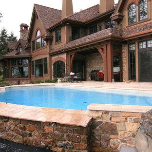 Foto de piscina de estilo americano, grande, a medida, en patio trasero, con adoquines de piedra natural