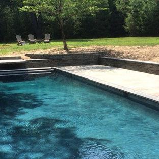 Ejemplo de piscina contemporánea con adoquines de piedra natural
