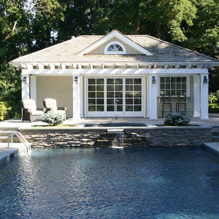 Photo of a large arts and crafts backyard rectangular lap pool in New York with a pool house and natural stone pavers.