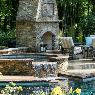 Modelo de piscina con fuente elevada, clásica, en patio trasero, con adoquines de ladrillo