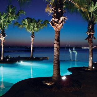 Esempio di un'ampia piscina a sfioro infinito tropicale personalizzata dietro casa con fontane e pavimentazioni in pietra naturale