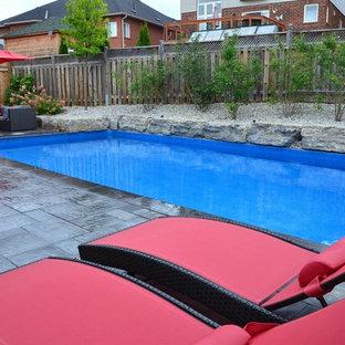 Foto de piscina alargada, clásica renovada, de tamaño medio, rectangular, en patio trasero, con adoquines de hormigón