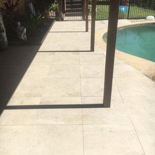 Diseño de piscina moderna, de tamaño medio, tipo riñón, en patio trasero, con suelo de baldosas