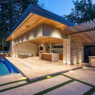 Esempio di una grande piscina moderna rettangolare dietro casa con una dépendance a bordo piscina e pavimentazioni in cemento