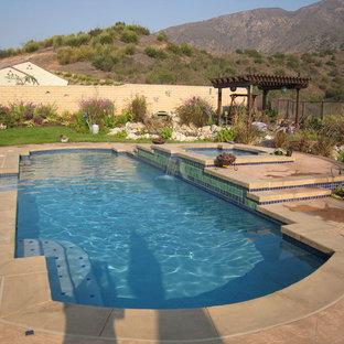 Esempio di una piscina naturale minimalista personalizzata di medie dimensioni e dietro casa con fontane e graniglia di granito