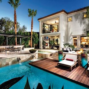 Foto de piscina con fuente clásica renovada, en forma de L, en patio trasero, con entablado