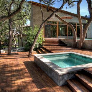 Idee per una piscina a sfioro infinito design rettangolare dietro casa con una vasca idromassaggio e pedane