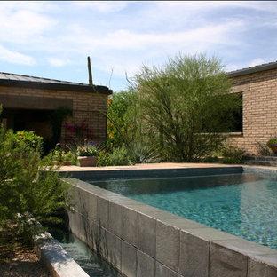 Diseño de piscina elevada, de estilo americano, de tamaño medio, rectangular, en patio trasero, con adoquines de hormigón