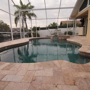 Imagen de piscinas y jacuzzis mediterráneos, grandes, tipo riñón, en patio trasero, con suelo de hormigón estampado