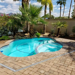 Photo of a small traditional backyard custom-shaped pool in San Diego with a hot tub.