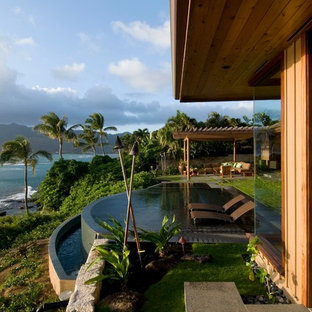 Ejemplo de piscina infinita, exótica, grande, redondeada, en patio trasero, con adoquines de hormigón