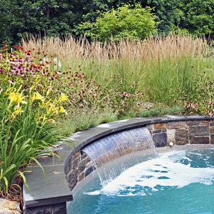 Idee per una grande piscina monocorsia country rotonda dietro casa con una dépendance a bordo piscina e pavimentazioni in pietra naturale