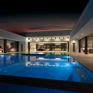 Ispirazione per una grande piscina minimalista rettangolare dietro casa con una vasca idromassaggio e piastrelle