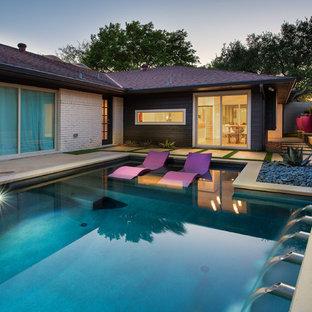 Imagen de piscina vintage, de tamaño medio, a medida, en patio trasero, con losas de hormigón