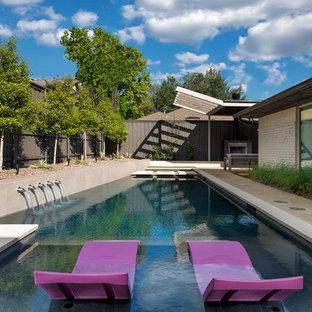 Ejemplo de piscina con fuente retro, de tamaño medio, rectangular, en patio trasero, con losas de hormigón