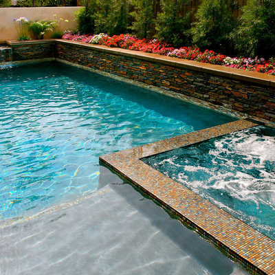 Mid-sized island style backyard stone and rectangular lap pool fountain photo in Los Angeles