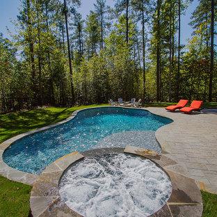 На фото: естественный бассейн среднего размера, произвольной формы на заднем дворе в стиле рустика с джакузи и мощением тротуарной плиткой