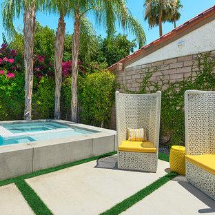 Modelo de piscina con fuente retro, pequeña, rectangular, en patio trasero, con losas de hormigón