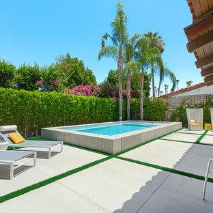 Aménagement d'une petite piscine arrière rétro rectangle avec un point d'eau et une dalle de béton.