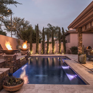Example of a mid-sized classic backyard stone and rectangular pool design in Phoenix