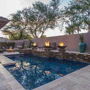 Ejemplo de piscina tradicional, de tamaño medio, rectangular, en patio trasero, con adoquines de piedra natural