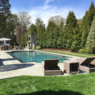 Mid-sized elegant backyard stamped concrete and rectangular lap pool photo in New York