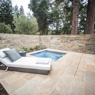 This is an example of a small country side yard pool in San Francisco with a hot tub and natural stone pavers.