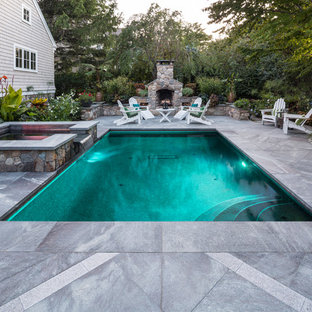 This is an example of a small traditional side yard rectangular lap pool in Portland Maine with a hot tub and natural stone pavers.