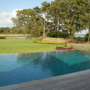 Imagen de piscina infinita, clásica renovada, de tamaño medio, rectangular, en patio trasero, con entablado