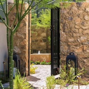 Ejemplo de piscina con fuente rústica, de tamaño medio, rectangular, en patio trasero, con granito descompuesto