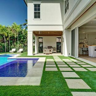 Ejemplo de piscina alargada, marinera, grande, a medida, en patio trasero, con adoquines de hormigón