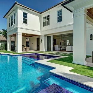 Modelo de piscina alargada, marinera, grande, a medida, en patio trasero, con adoquines de hormigón