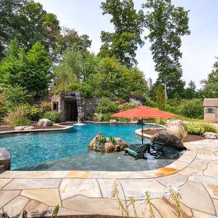 Cette image montre une piscine arrière traditionnelle sur mesure avec un point d'eau et des pavés en pierre naturelle.