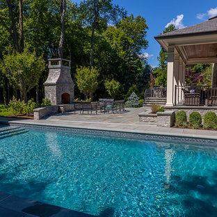 Esempio di una grande piscina monocorsia tradizionale personalizzata dietro casa con fontane e pavimentazioni in cemento