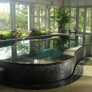 Ejemplo de piscinas y jacuzzis infinitos, contemporáneos, grandes, interiores y tipo riñón, con adoquines de piedra natural