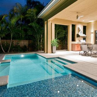 Diseño de piscina con fuente actual, pequeña, a medida, en patio trasero, con adoquines de hormigón