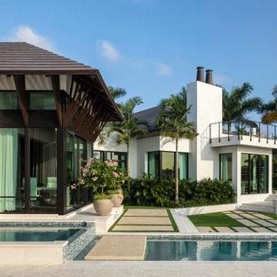 Modelo de piscina infinita, mediterránea, grande, en forma de L, en patio trasero, con adoquines de piedra natural