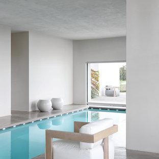 Esempio di una piscina coperta design rettangolare con pavimentazioni in cemento