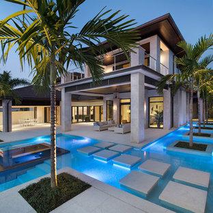 Modelo de piscina exótica, a medida, en patio trasero, con suelo de hormigón estampado
