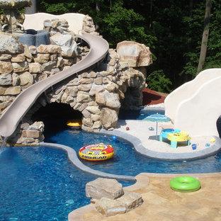 Ejemplo de piscina con tobogán contemporánea, grande, a medida, en patio trasero, con adoquines de piedra natural