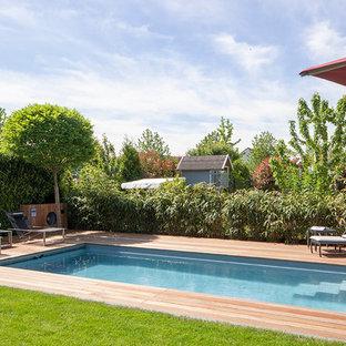 Ejemplo de piscina con fuente alargada, mediterránea, de tamaño medio, rectangular, en patio lateral, con entablado