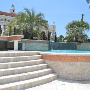 Ejemplo de piscina con fuente infinita, mediterránea, extra grande, a medida, en patio trasero, con suelo de baldosas