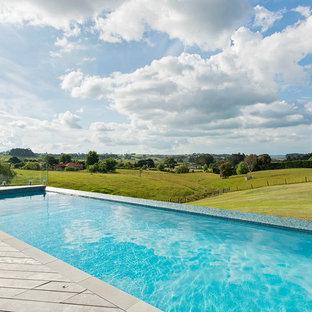 Esempio di una piscina a sfioro infinito contemporanea rettangolare dietro casa con pedane