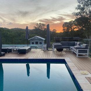 Idée de décoration pour une grand piscine sur une terrasse en bois hors-sol et arrière minimaliste avec un aménagement paysager autour d'une piscine.