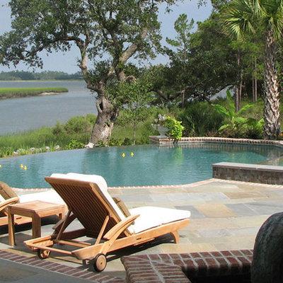 Hot tub - large tropical backyard brick and round aboveground hot tub idea in Charleston