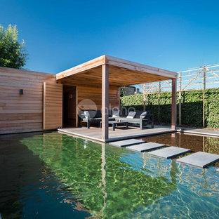 """Ispirazione per una grande piscina naturale design a """"L"""" nel cortile laterale con una dépendance a bordo piscina e pedane"""